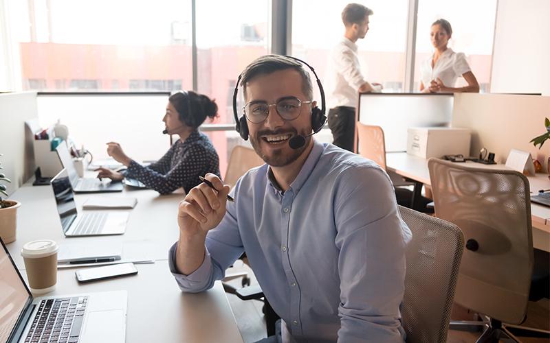 Glimlachende-man-met-headset-achter-computer-in-meeting