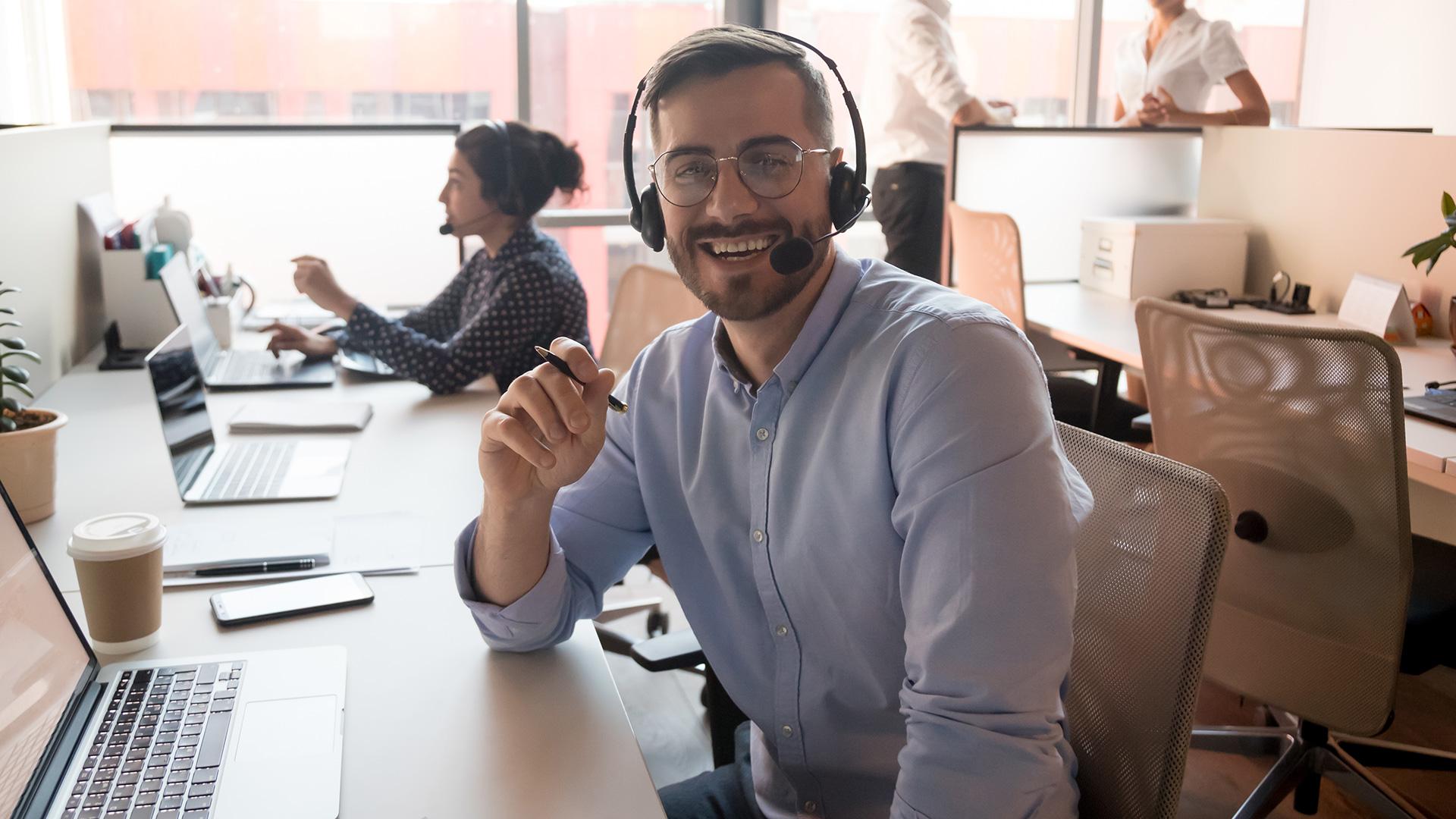 Klantcontact-medewerker-glimlachend-aan-bureau
