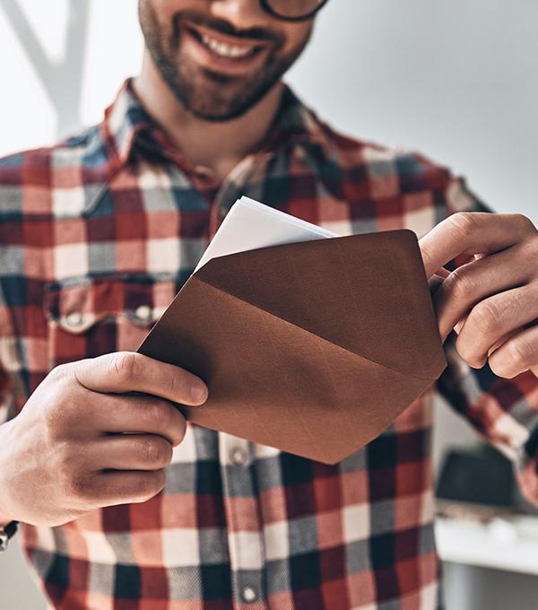 Man-opent-enveloppe-en-glimlacht